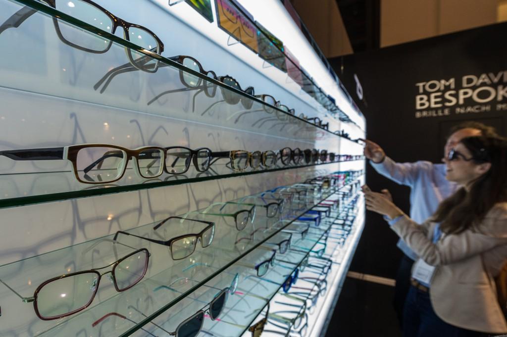 Viele Brillen in einem Regal, davor ein Kunde.